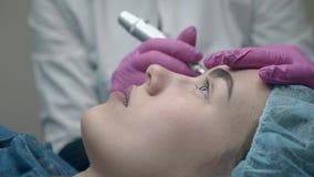 Kosmetologen färgar ögonbrynet för den unga kvinnan i svart nära sikt lager videofilmer