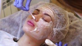 Kosmetologen förbereder kräm- bedövningsmedel för framsidaflickor för skönhet stock video