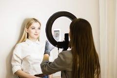 Kosmetologen fotograferar hans arbete på en mobiltelefon Två flickor i en skönhetsalong Cirkellampa för makeupkonstnärer Framsida arkivbilder