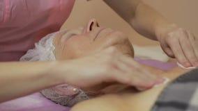 Kosmetologen gör ansiktsbehandlingen som rentvår och exfoliating arkivfilmer