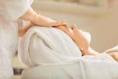 Kosmetologen g?r ansikts- massage till flickan fotografering för bildbyråer
