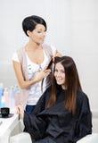 Kosmetologen klipper hår av kvinnan i friseringsalong arkivfoton