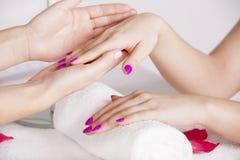 Kosmetologen kontrollerar händerna för klient` s Arkivbild