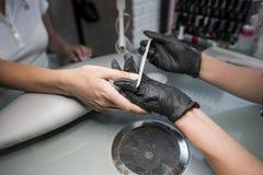 Kosmetologen maler spikastången för en manikyr i skönhetsalongen Fingret spikar behandling som maler och polerar royaltyfria bilder