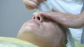 Kosmetologen räcker att slå framsidan av klienten Härlig flicka för ansikts- massage Stående av en ung kvinna i skönheten lager videofilmer