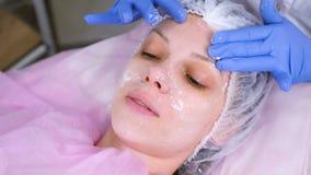 Kosmetologen sätter maskeringen på kvinnans framsida Rengörande framsida lager videofilmer