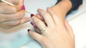 Kosmetologen som applicerar polermedel, spikar till kvinnor spikar stock video