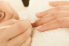 Kosmetologen som förbereder sig, spikar för manikyr, driftiga tillbaka nagelband arkivbild