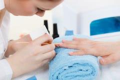 Kosmetologen som förbereder sig, spikar för manikyr, driftiga tillbaka nagelband royaltyfria bilder