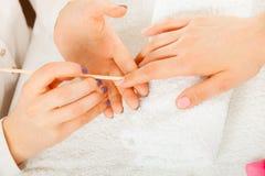 Kosmetologen som förbereder sig, spikar för manikyr, driftiga tillbaka nagelband arkivbilder