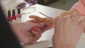 Kosmetologen som gör manikyr för lite, behandla som ett barn flickan på skönhetbrunnsortsalongen arkivfilmer