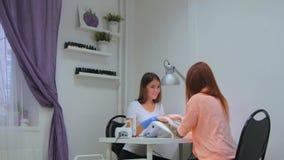 Kosmetologen som talar med klienten om nailcaren och, spikar design Arkivfoton