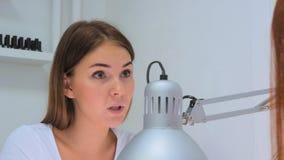 Kosmetologen som talar med klienten om nailcaren och, spikar design Fotografering för Bildbyråer