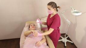Kosmetologen tar bort h?r fr?n h?nderna av en ung flicka med sockerdeg sockra arkivfilmer