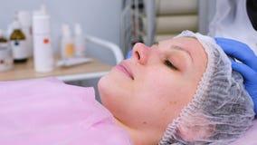 Kosmetologen tvättar kvinnans framsida genom att använda bomullsblock från maskering Rengörande framsida arkivfilmer