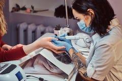 Kosmetologförlage i handskar som applicerar för att spika drillborren för att klippa och ta bort nagelband Maskinvarumanikyr i en royaltyfri foto