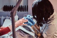 Kosmetologförlage i handskar som applicerar för att spika drillborren för att klippa och ta bort nagelband Maskinvarumanikyr i en arkivbilder