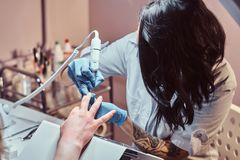 Kosmetologförlage i handskar som applicerar för att spika drillborren för att klippa och ta bort nagelband Maskinvarumanikyr i en fotografering för bildbyråer