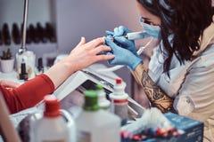 Kosmetologf?rlage i handskar som applicerar f?r att spika drillborren f?r att klippa och ta bort nagelband Maskinvarumanikyr i en fotografering för bildbyråer