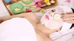 Kosmetologhand som tar bort gurkan från kvinnaögon stock video