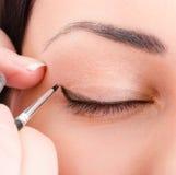 Kosmetologkonstnär som applicerar makeup Arkivbild