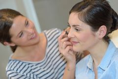 Kosmetologstudenter som arbetar under sminkgrupper arkivfoto
