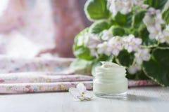 Kosmetyczna śmietanka z kwiatami na zaświeca kamiennego tło Obrazy Stock