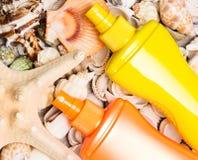Kosmetyczni sunscreen produkty z rozmaitością skorupy i rozgwiazda Obrazy Stock