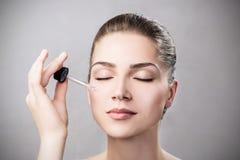 Kosmetyka nafciany stosować na twarzy młoda kobieta Obrazy Stock