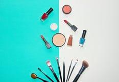Kosmetyki biali i błękitny tło z uzupełniali artystów przedmioty: pomadka, oko cienie, tusz do rzęs, eyeliner, concealer, gwoździ fotografia stock