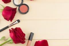 Kosmetyki dekorowali z czerwonymi różami na lekkim drewnie Fotografia Stock