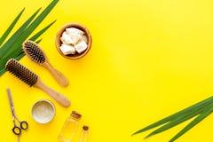 Kosmetyki dla włosianej opieki z jojoba, argan lub kokosowym olejem w butelce, grępla, nożyce na żółtym tło odgórnego widoku mock fotografia royalty free