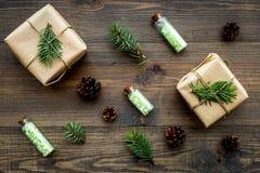 Kosmetyki z sosnowym olejem Zdrój sól w butelek blisko zawijających pudełkach, świerczyna rozgałęzia się, pinecones na drewnianym Fotografia Royalty Free