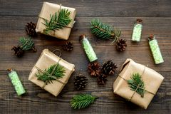 Kosmetyki z sosnowym olejem Zdrój sól w butelek blisko zawijających pudełkach, świerczyna rozgałęzia się, pinecones na drewnianym Zdjęcia Royalty Free
