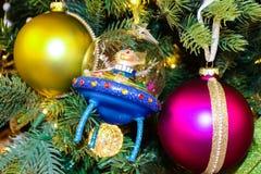 Kosmita daje pokojowi podpisuje wewnątrz błękitną obcy rakietę na tradycyjnej choince z czerwonych i magenta ornamentami Obrazy Royalty Free