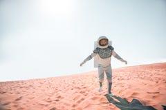 Kosmonaut die gedachte lege woestijn lopen Stock Foto