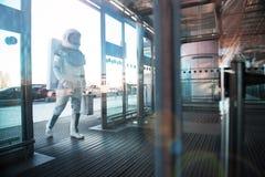 Kosmonauta wchodzić do wielkiego nowożytnego budynek zdjęcie royalty free