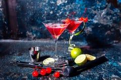 Kosmopolitisk körsbärsröd martini coctail som tjänas som förkylning med limefrukt och is arkivfoton