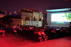 Kosovars und fremde Besucher nehmen ihre Sitze auf einer angehobenen Plattform, um einen Dokumentarfilm während Dokufest in Prizr Lizenzfreies Stockfoto