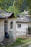 Kosovo, Bulgaria - July 21, 2017: unidentified old Bulgarian woman sits in front of her mean house Stock Images