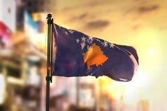 Kosovo Flag Against City Blurred Background At Sunrise Backlight Stock Image