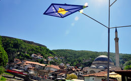 Kosovo flag with a beautiful view of the old part of Prizren. Metal construction with flags of the participants in the Dokufest at Stone Bridge in Prizren Stock Photos