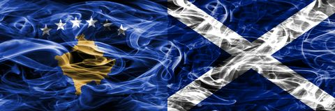 Kosovo vs Scotland smoke flags placed side by side stock photography