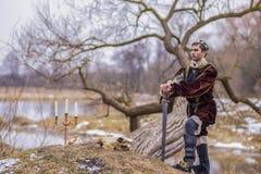 Kostüm-Spiel Art Photography Einsamer Ritter In Medieval Outfit, das in Forest Outdoors Against River On-Hintergrund aufwirft lizenzfreie stockfotos