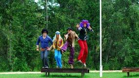 Kostümierte Erwachsene, die in einer Luft springen Stockbild