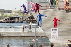 Kostümierte Erwachsene springen in Pool Stockfotografie