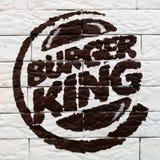 Kostanay, Cazaquistão, 11-25-2018, logotipo de Burger King pintou em uma parede de tijolo em um restaurante Primeira jornada Arti foto de stock royalty free