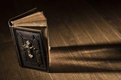 Kostbare antike Bibel auf einem hölzernen Desktop stockfotografie