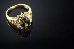 Kostbare Edelsteine und Goldring im Schwarzen Stockbild