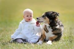 Kostbare het Meisjeszitting van de 1 éénjarigebaby buiten met Huisdierenhond Stock Foto's